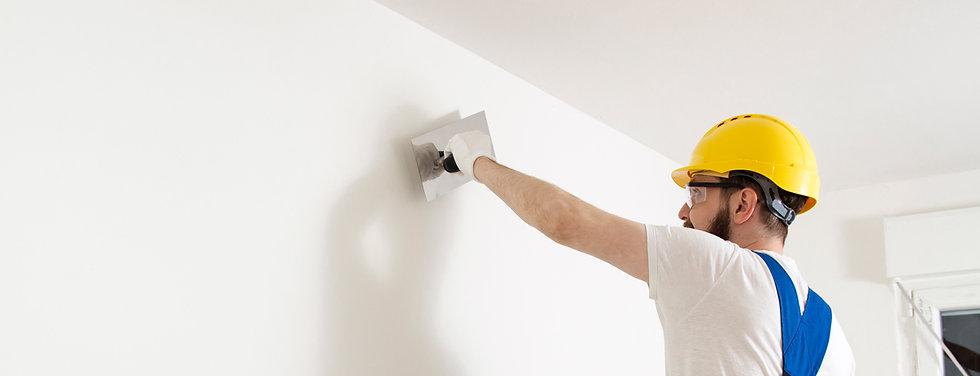Contractor repairing drywall