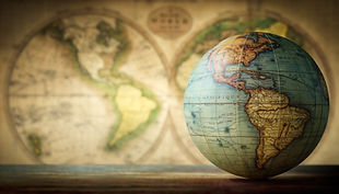 Old globe on vintage map background. Sel
