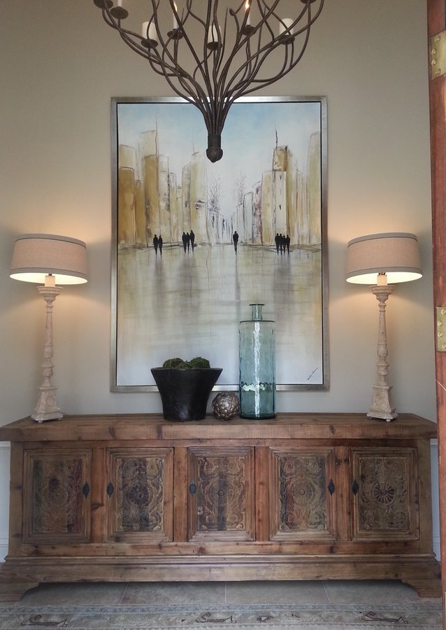 This entry blends contemparary art with a rustic console piece and an antique rug.