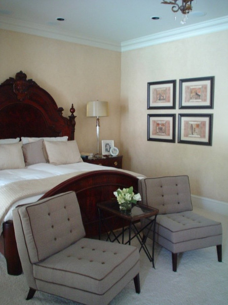 Contemporary chairs are paired with this traditional Henredon bed.