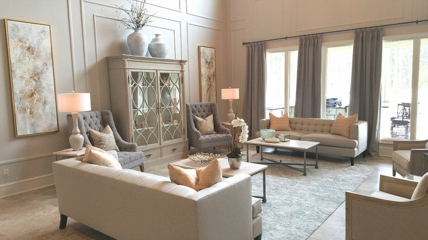 The beautiful cabinet is the focal point of this big wall.  Gold finishes on the frames and end tables add brightness.