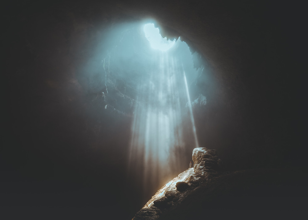 A stream of light shining down at a cave opening.