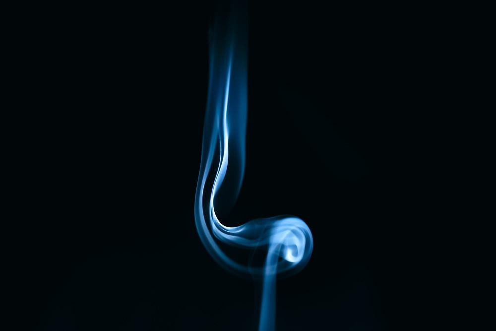 A blue stream of smoke on a black background.