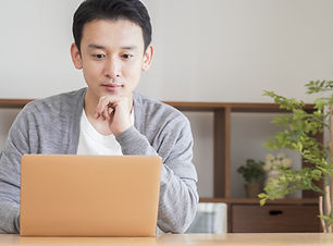 Asian man using a computer in the living room.jpg