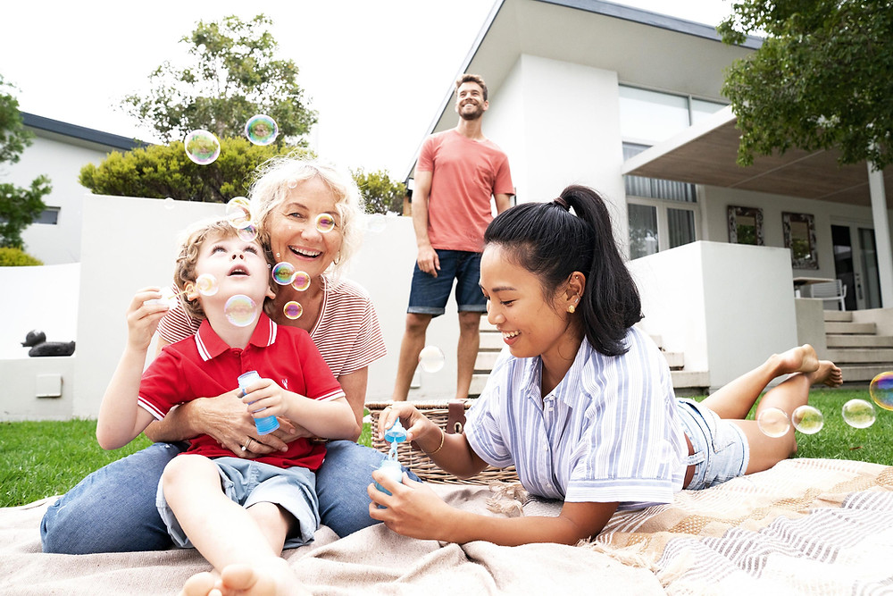 Family laying on a picnic blanket outside blowing bubbles with children