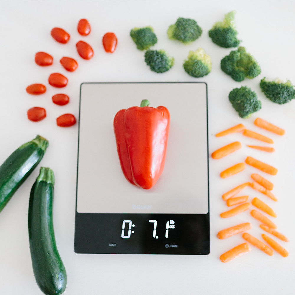 Kitchen scale being used to weigh bell peppers, carrots, broccoli, tomatoes and cucumbers