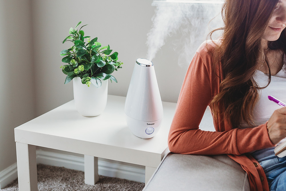 Woman on couch with the Beurer essential oil diffuser misting on a side table