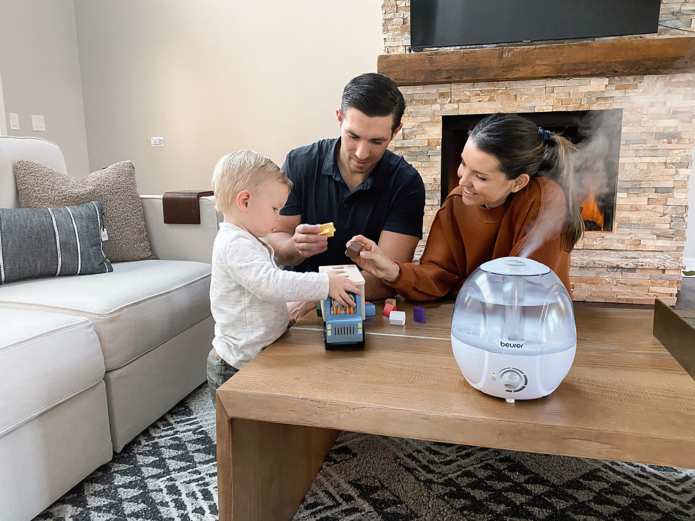 Parents with their baby on the living room coffee table. The LB27 is features on the coffee table as well