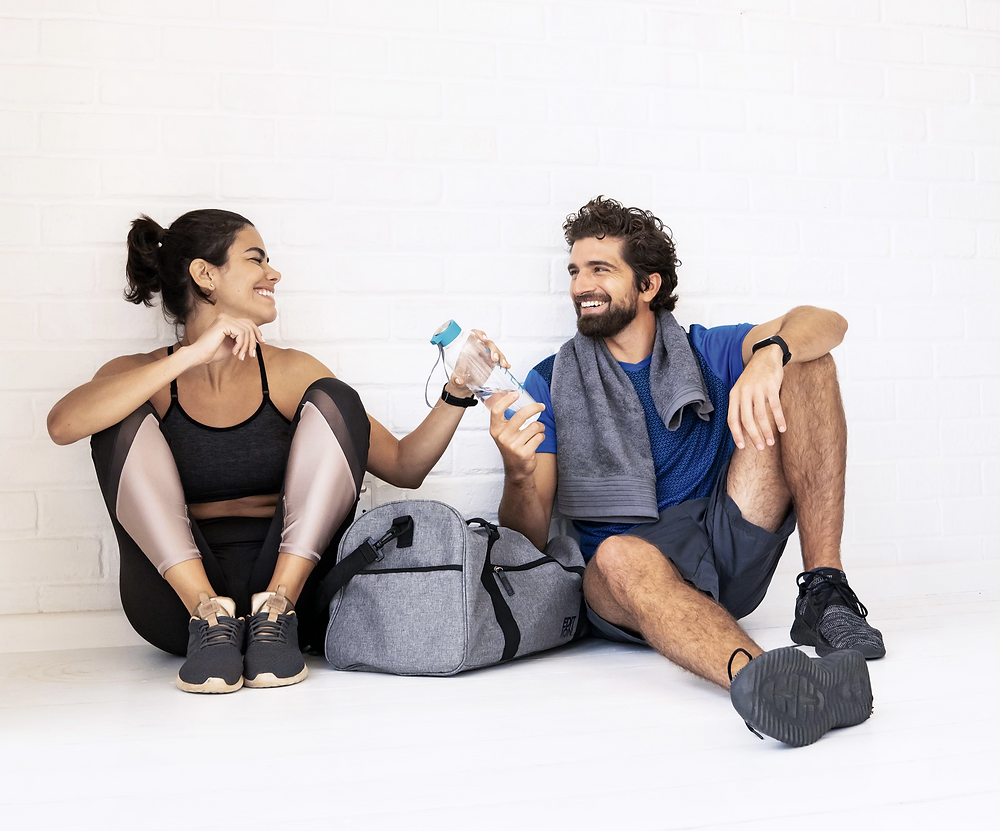 Friends motivating each other. Workout motivation. Man and woman laughing and handing water to each other after workout.