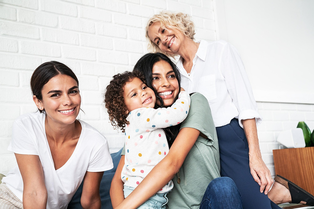 Older woman, two middle aged women, and a little girl hugging each other