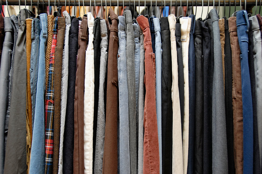 A rack of mens pants in a second hand sh