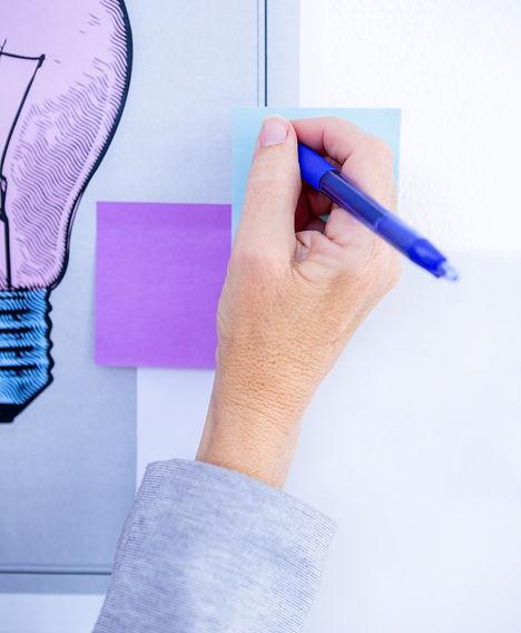creative-businesswoman-writing-on-post-i