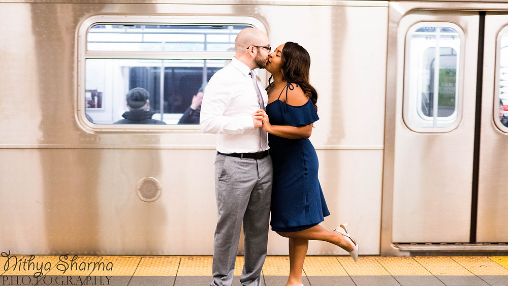 Couple kissing in front of NYC subway