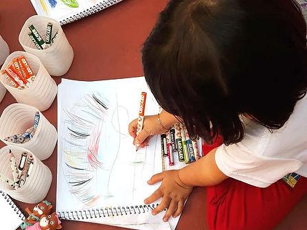 Criança sentada no chão desenhando