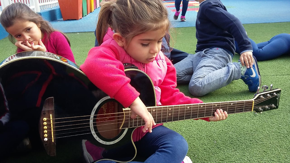 Aluna tocando violão