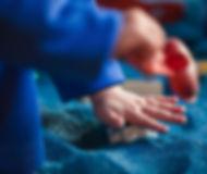 Criança brincando com areia azul