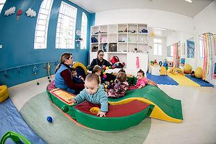 Espaço intrno do berçário com bebês brincando em piscina de bolinhas.