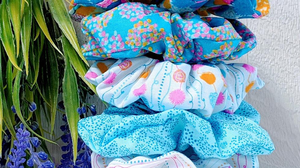 Set of 5 multicoloured pom pom patterned hair scrunchies.