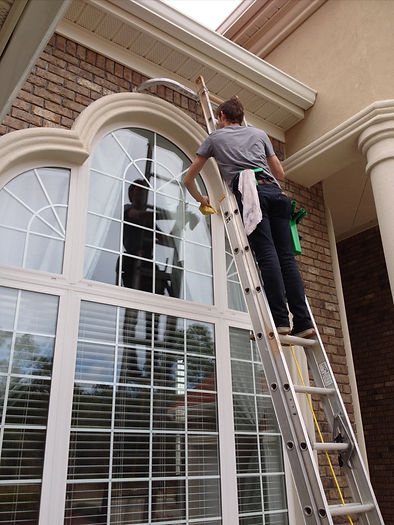Person on a ladder cleaning windows.