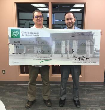 Jean-Pierre Boutin, président du Salon du Livre reçoit 5000$ de la main de Pierre Richard, directeur de la Caisse populaire de Hearst.