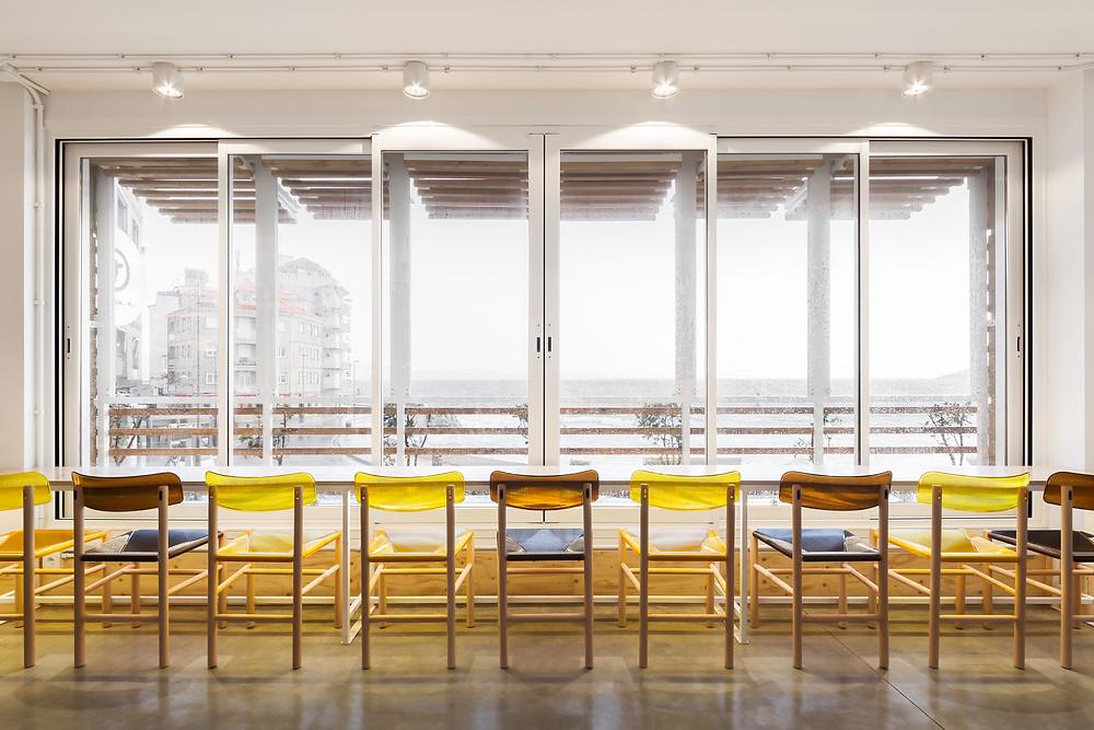 espaço aberto restaurante café iluminação Tromilux projetor saliente branco marca nacional cadeiras douradas vista mar