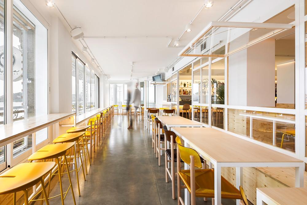 espaço aberto restaurante café iluminação Tromilux projetor saliente branco marca nacional cadeiras douradas mesas madeira