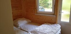 malá ložnice vedle obýváku s dvermi ven.