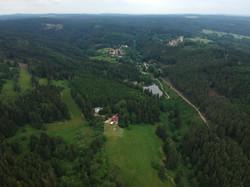 Lesní vila a velkorysá chata v popředí