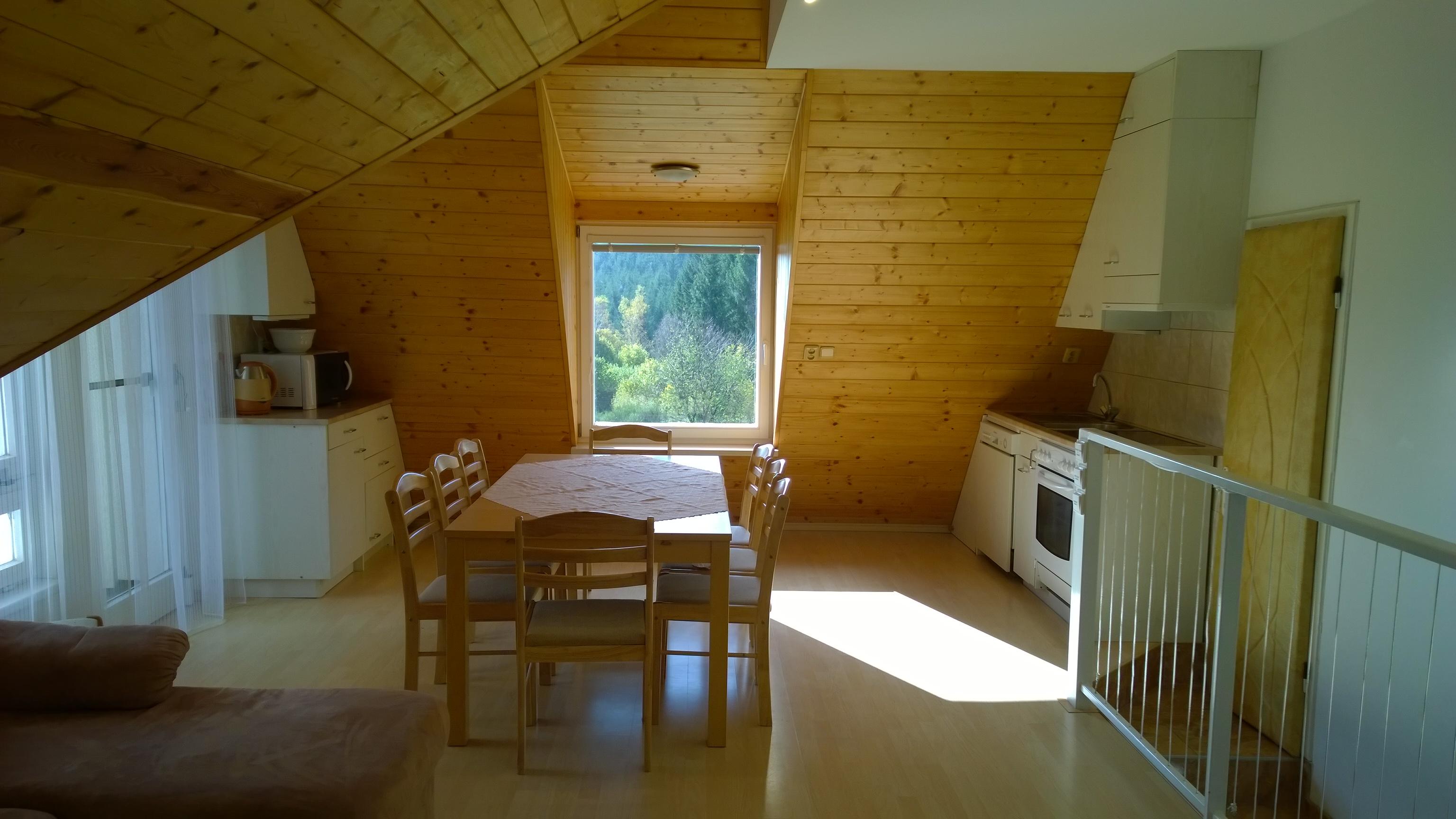 ap. B obývák s kuchyní a balkónem, stul pro až 12 osob, vstupní schody a vchod do ložnice ap. C, dvo