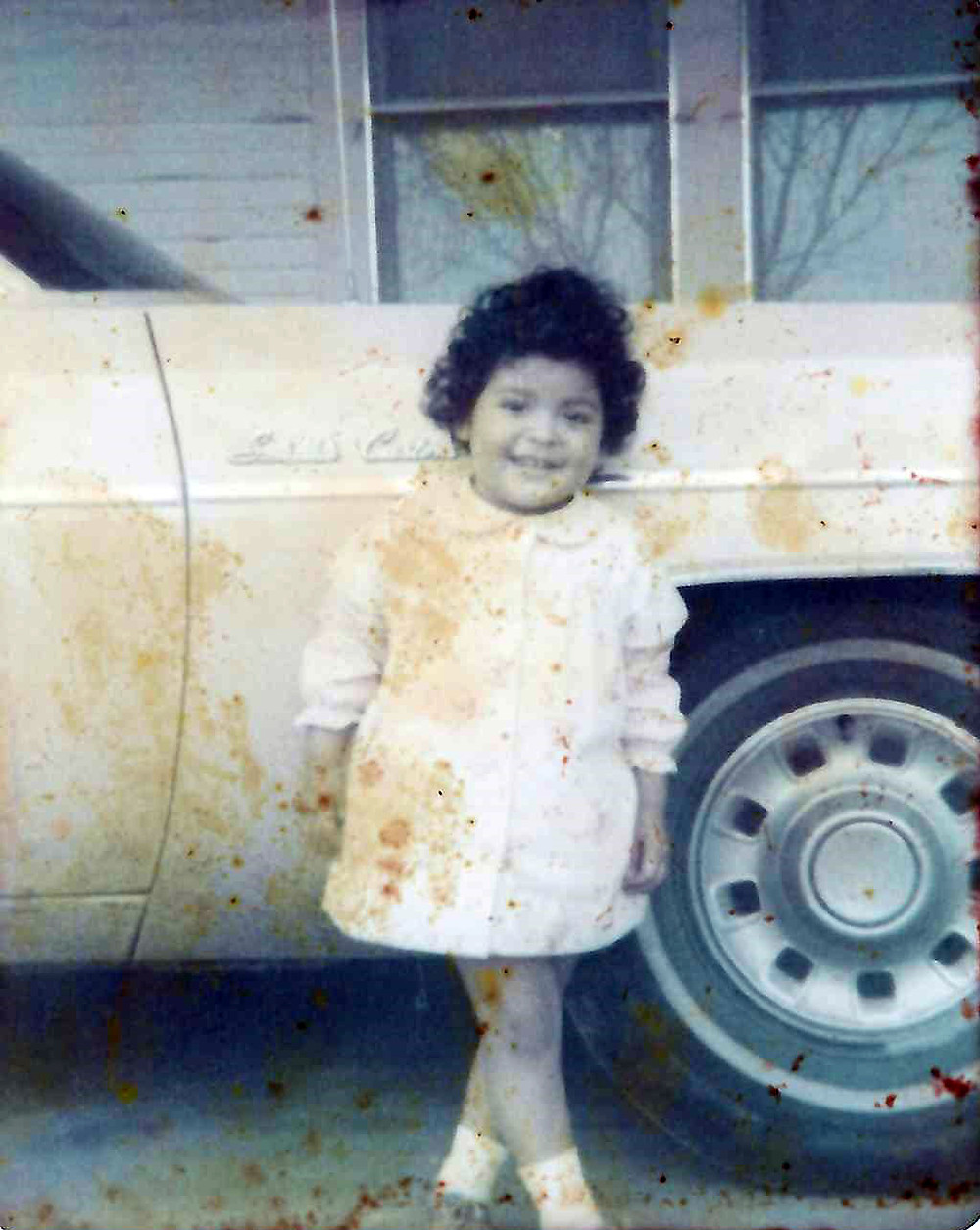 little girl in front of a yellow station wagon