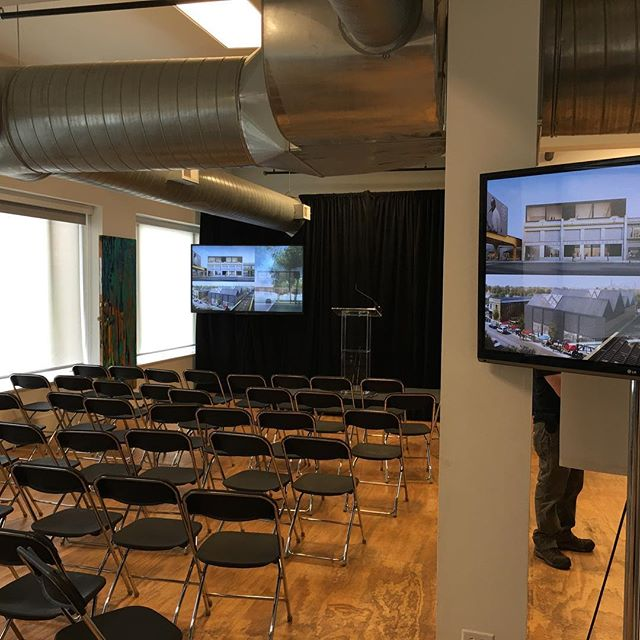 Two tv monitors, a pipe and drape wall, sound system, and stage set for an event today!