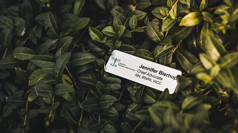 Libellen Patient Advocates metal name tag laying in the bushes. The name tag reads, Jennifer Bierhup, Chief Advocate, RN iRNPA WCC CCM.