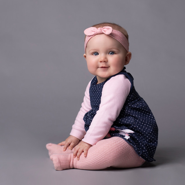 cute baby sitting with pink head band