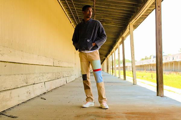 Black fashion model wearing Sync Denim pants at a warehouse location shot by MXJ Photography