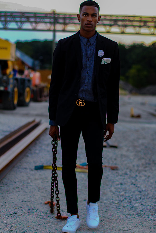 Black fashion model wearing Gucci belt and suit and styled as a high end model shot by MXJ Photography at a construction site