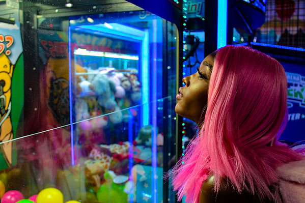 Black female model posing at an arcade with neon lighting beauty shot by MXJ Photography