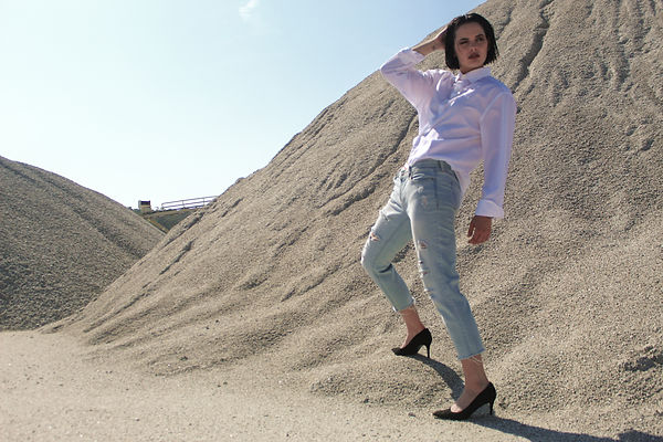 Female fashion model styled in Calvin Klein on location at a landfill shot by MXJ Photography