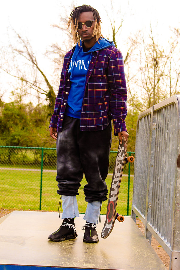 Black fashion model wearing John Geiger shoes and styled as urban fashion skater at a skate park shot by MXJ Photography