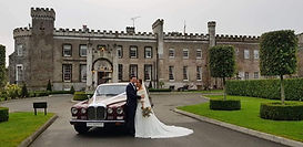 Wine coloured vintage Daimler DS Wedding Car outside the beautiful Bellingham Castle in County Louth Ireland with wedding couple standing beside the car posing for a picture