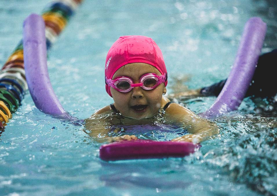 Girl learning to swim using a float and noddle at Northern Arena