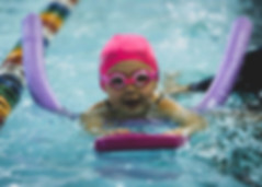 Child kicking with kick board and noodle wearing cap and goggles