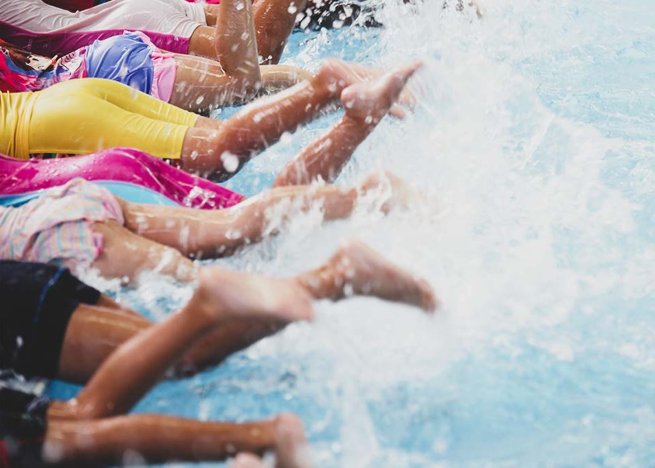 Children kicking on side of the pool splashing
