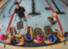 Swim instructor teaching kids how to swim with kick boards