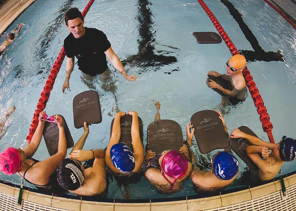 Swim instructor teaching kids how to swim with kick boards