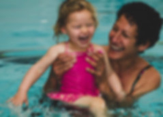 women and child laughing in the swimming pool
