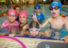 Children smiling while learning to swim