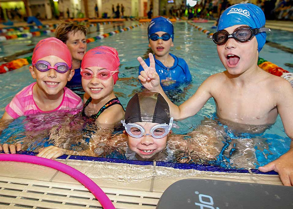Children in swimming lesson with swimming instructor