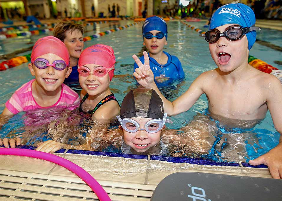 kids smilling at camera in swimming lesson