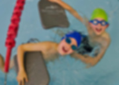 Two boys learning to swim with kick boards