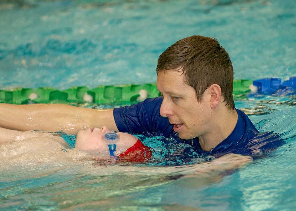 Dean Kent teaching backstroke to child